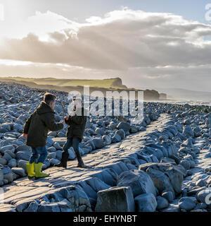 Deux garçons ayant une épée prétendre lutter avec des bâtons sur la plage Banque D'Images