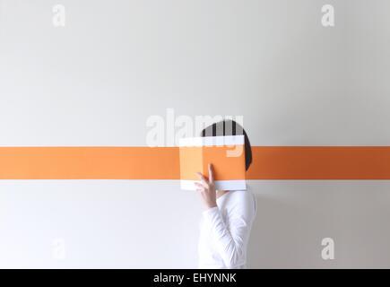 Vue latérale d'une femme mature cachant son visage derrière un livre Banque D'Images