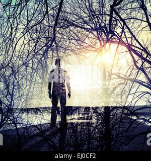 Double exposition conceptuel abstrait collage photo, l'homme debout sur le littoral, soleil et les branches d'arbres Banque D'Images