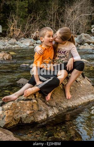 Neuf ans, fille de donner son frère de sept ans une étreinte et un baiser alors qu'il était assis sur un rocher Banque D'Images
