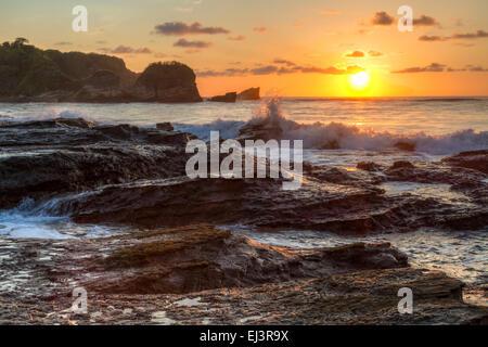 Les vagues déferlent sur le contre-jour côte rocheuse de Playa Pelada au coucher du soleil sur la côte Pacifique Banque D'Images