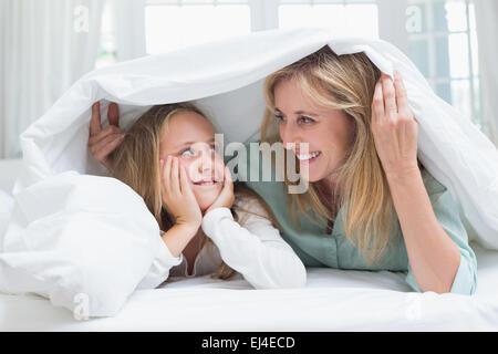 Mère et fille se regardant sous la couette Banque D'Images