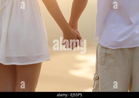 Gros plan d'une vue arrière d'un couple en train de marcher et tenir la main sur la plage au lever du soleil Banque D'Images
