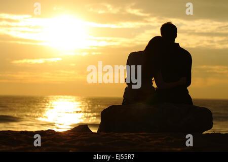 Silhouette Couple cuddling et regarder bien au coucher du soleil sur la plage Banque D'Images