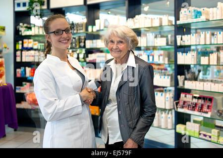 Smiling friendly female pharmacist portant des lunettes aider une dame âgée dans sa pharmacie ou droguerie shaking Banque D'Images