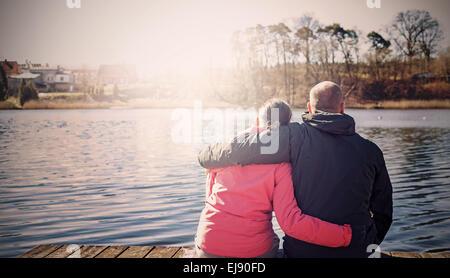 Filtrée Retro photo d'un couple sitting on wooden pier par lac. Banque D'Images