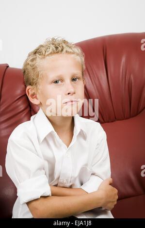 Jeune garçon blond sur canapé Banque D'Images