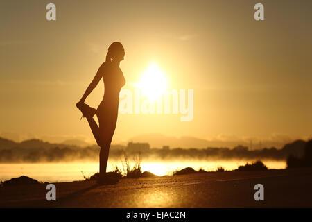 Silhouette d'une femme de remise en forme stretching profil au lever du soleil avec le soleil en arrière-plan Banque D'Images