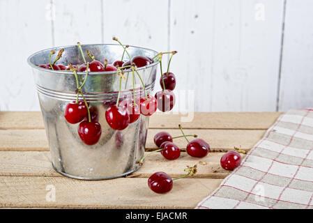 Les cerises dans un petit seau en métal sur la table en bois Banque D'Images