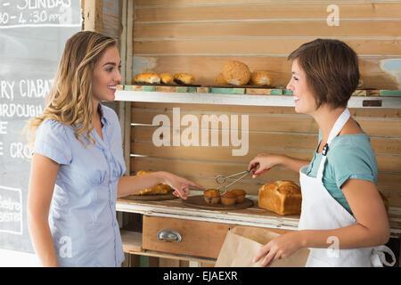 Jolie muffin waitress au client Banque D'Images