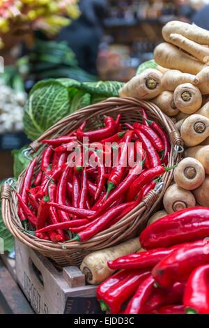 Un panier de piments rouges affichés sur un kiosque de légumes dans un contexte de panais et chou Banque D'Images