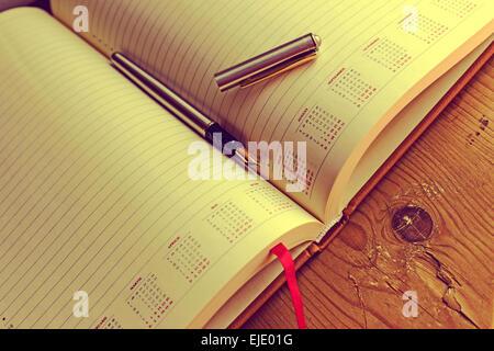 Ouvrir un journal intime avec stylo en elle, placé sur une table en bois. Traitement vintage. Banque D'Images