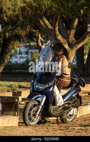 Une paire s'embrasser sur un vélo dans le parc. Banque D'Images