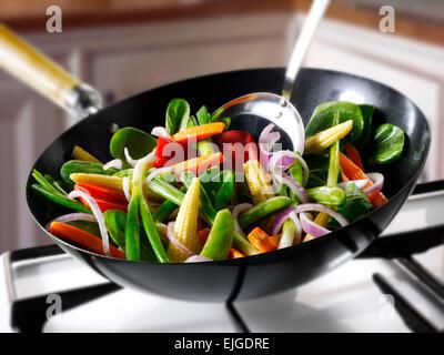 La cuisson des légumes sautés au wok Banque D'Images