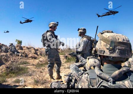 Les soldats de l'armée américaine d'attendre d'être ramassé par les hélicoptères Black Hawk UH-60 au sud de Balad Banque D'Images