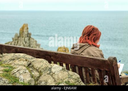 Jeune femme rousse assise sur un banc le long de la côte sud, Polperro Path au sud-est de Cornwall, Angleterre du Banque D'Images