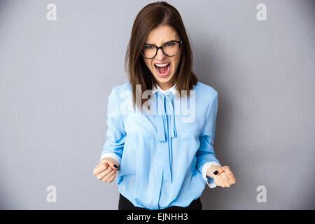 Angry businesswoman criant sur fond gris. En chemise bleue et portant des lunettes. Looking at camera Banque D'Images