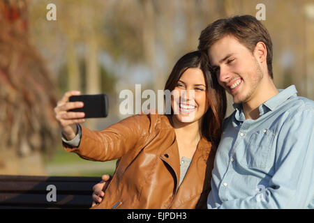 Heureux couple taking photos selfies assis dans un banc dans un parc Banque D'Images