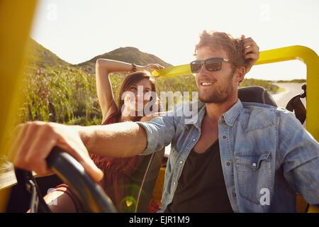 Man man driving car un jour d'été. Jeune couple aimant on road trip. Banque D'Images
