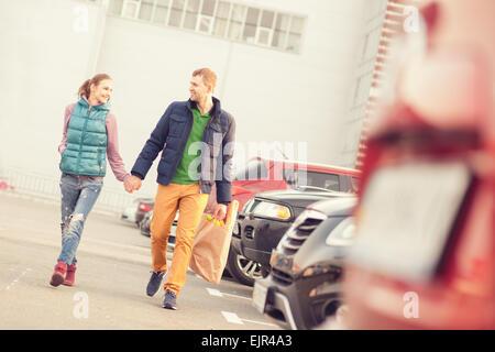 Couple en train de marcher sur le parking après le magasinage Banque D'Images