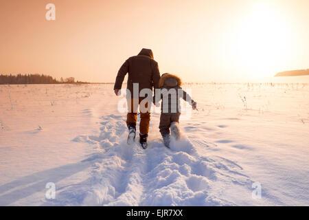 Mari et père fils walking in snowy field Banque D'Images