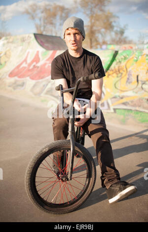 Caucasian man riding bicycle BMX au skate park Banque D'Images