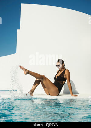 Mixed Race woman in swimsuit splashing in swimming pool Banque D'Images