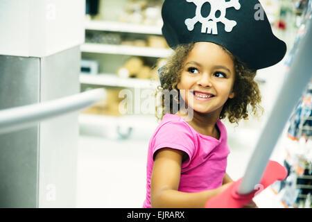 Mixed Race girl playing Dress-up avec chapeau de pirate et l'épée Banque D'Images