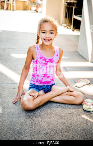Mixed Race girl assis les jambes croisées sur le trottoir Banque D'Images