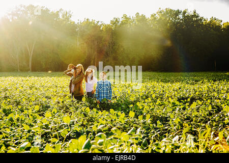 Caucasian family standing in crop field on farm Banque D'Images
