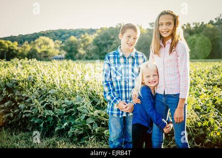 Des enfants de race blanche debout dans le champ de la récolte à la ferme Banque D'Images