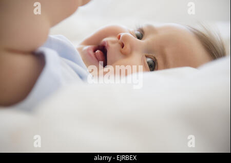 Close up of mixed race baby laying on bed Banque D'Images