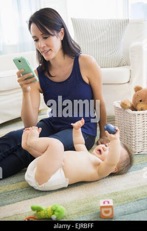 Mixed Race mother using cell phone avec bébé sur marbre Banque D'Images