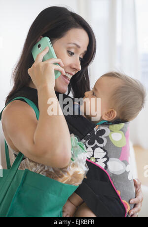 Mixed Race mother carrying baby et talking on cell phone Banque D'Images