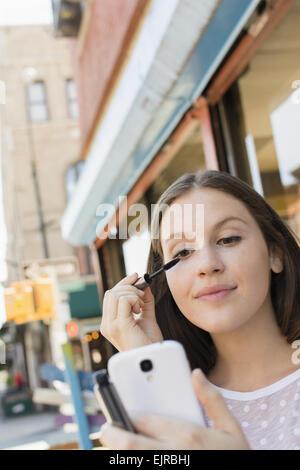 Caucasian woman applying makeup dans un téléphone cellulaire Banque D'Images