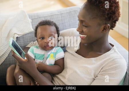 La mère et le fils noir using cell phone on sofa Banque D'Images