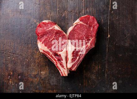 Forme de coeur la viande crue Ribeye Steak entrecote sur fond de bois Banque D'Images