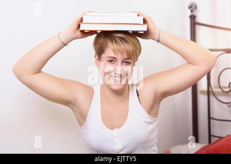 Jolie jeune femme heureuse de prendre une pause dans le cadre de ses études collégiales balancing books sur sa tête Banque D'Images