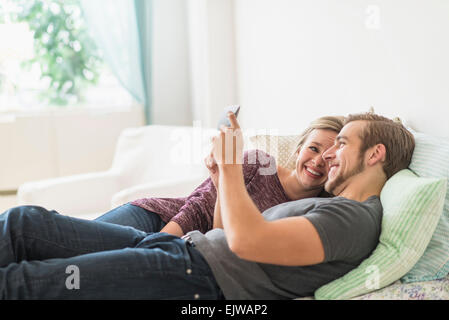 Smiling couple lying on bed and using digital tablet Banque D'Images