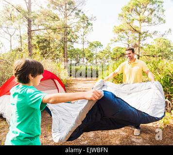USA, Floride, Jupiter, père et fils (12 et 13) la préparation de sac de couchage pour le camping Banque D'Images
