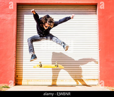 USA, Floride, West Palm Beach, l'homme sautant sur planche contre porte de garage fermé Banque D'Images