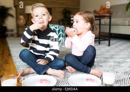 Frère et soeur (6-7) (4-5) eating cookies dans la salle de séjour Banque D'Images