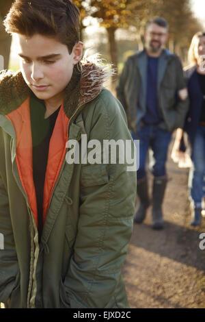 Teenage Boy Walking in Country Road, Parents en arrière-plan