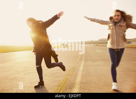 Teenage Girls Running with Arms Outstretched Banque D'Images