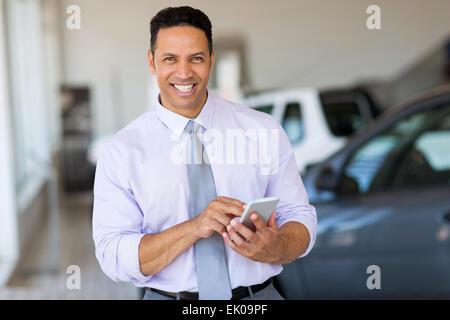 Bel homme d'âge moyen à l'aide de smart phone at car dealership Banque D'Images