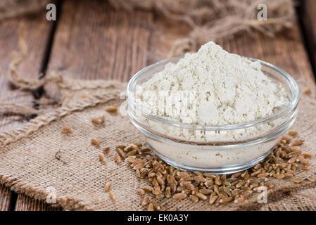 Petit bol avec la farine d'épeautre et des graines entières sur fond de bois Banque D'Images