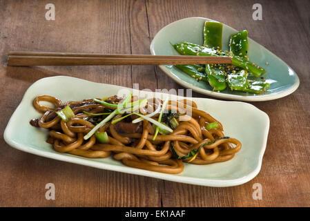 Nouilles udon sautées avec bok choy, pleurotes et échalotes frites et haricots verts à l'ail et le sésame. Banque D'Images