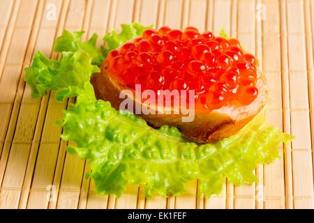 Du pain avec du caviar rouge sur une serviette en bambou Banque D'Images