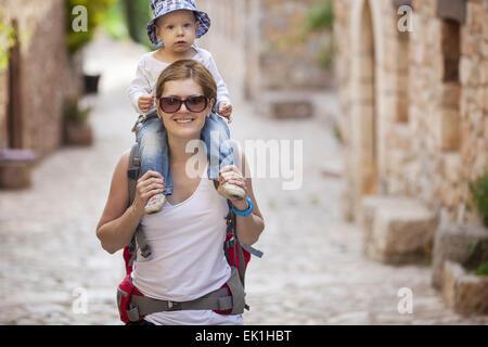 Young Caucasian woman tourist portant son petit fils sur les épaules Banque D'Images