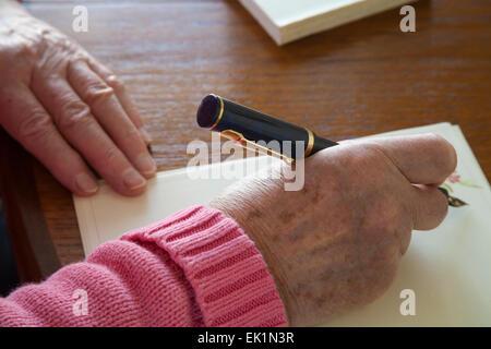 Close up femme âgée à l'aide de stylo pour écrire une lettre de remerciements Banque D'Images